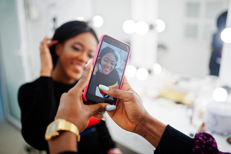 Hairstylist taking camera photo of client for social media marketing campaign